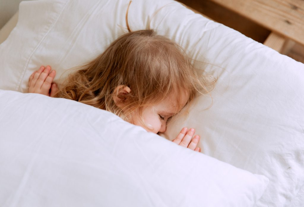 photo-of-child-laying-on-bed-3933069